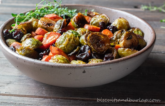horizontal shot of roasted brussel sprouts in pottery bowl
