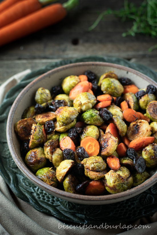 vertical shot of a bowl of roasted brussel sprouts with carrots