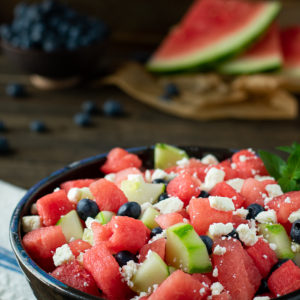 watermelon salad in bowl with watermelon & blueberries behind