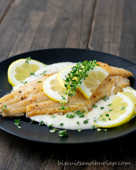catfish on black plate with lemons and sauce