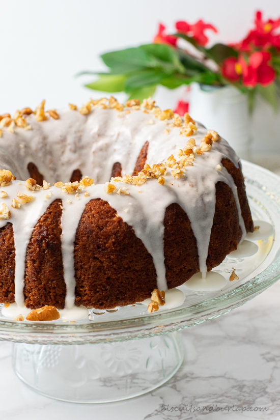 coffee cake on stand with red flowers in background