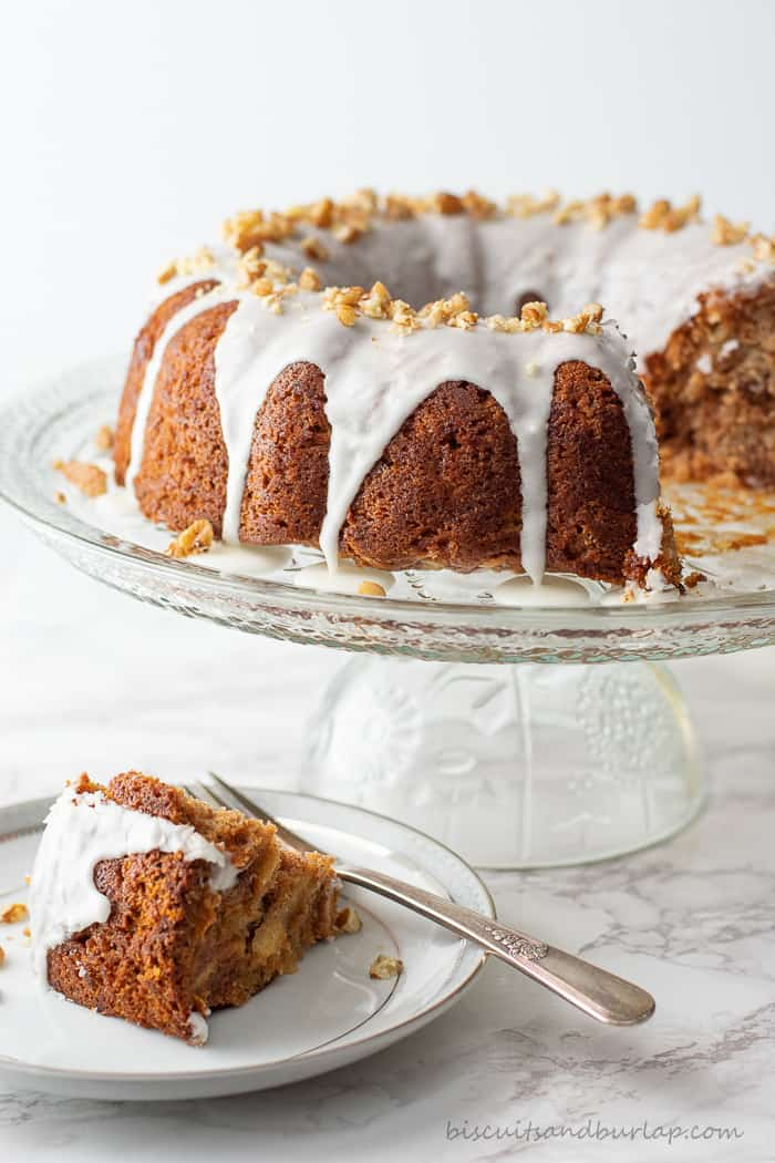 apple cider coffee cake on cake stand with slice on plate