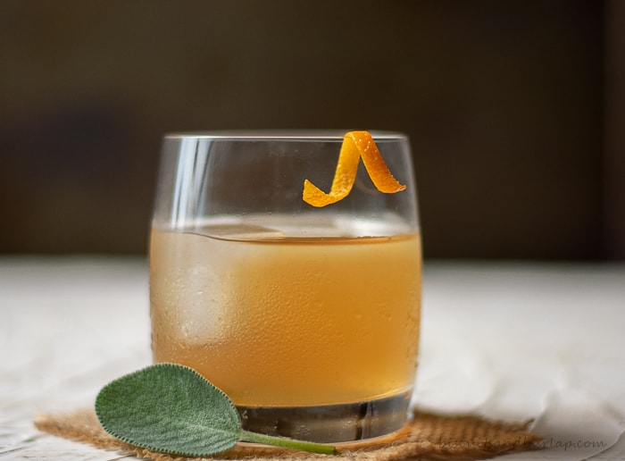 single bourbon cocktail with orange twist & sage leaf