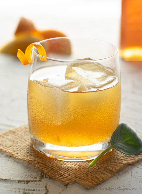 bourbon cocktail with oranges & honey bottle in background