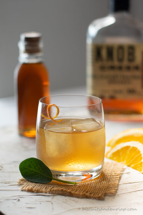 cocktail with honey, bourbon & orange behind it