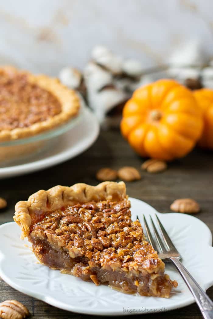 slice of pecan pie with whole pie and small pumpkin behind