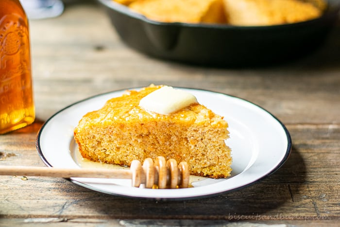 slice of sweet potato cornbread on plate with honey and butter on top
