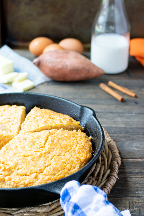 vertical shot of sweet potato cornbread in skillet with eggs and buttermilk behind