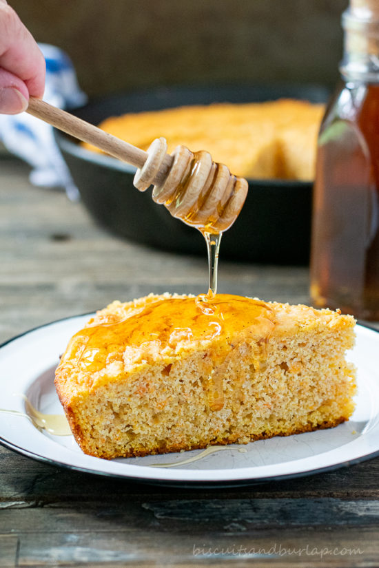 slice of sweet potato cornbread with honey dripping