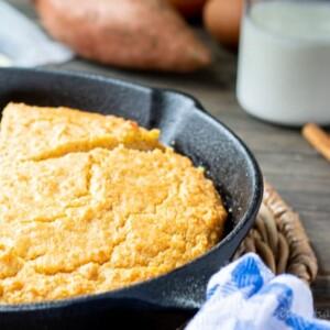 sweet potato cornbread in skillet with butter, buttermilk, sweet potato & cinnamon sticks behind