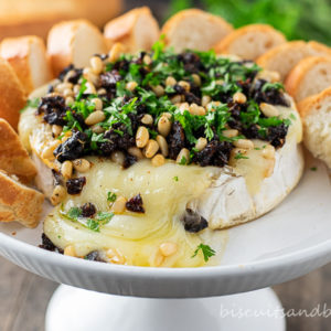 baked brie cheese on white plate with crostini