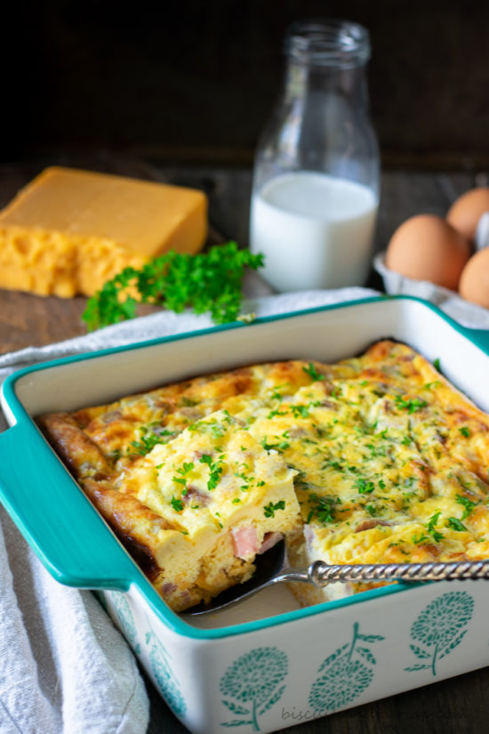keto breakfast casserole with cheese, eggs and milk behind