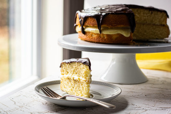 slice of boston cream pie on plate with whole cake behind