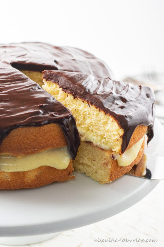 slice of boston cream pie being taken out of whole cake