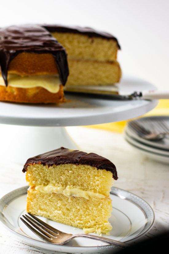 slice of boston cream pie on plate with fork and cake in background