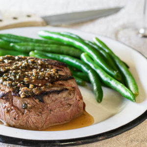 filet mignon sauce over steak with green beans and fork