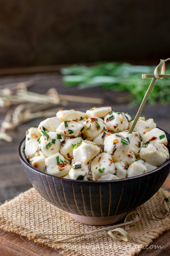 vertical shot of bowl of mozzarella pearls with herbs behind