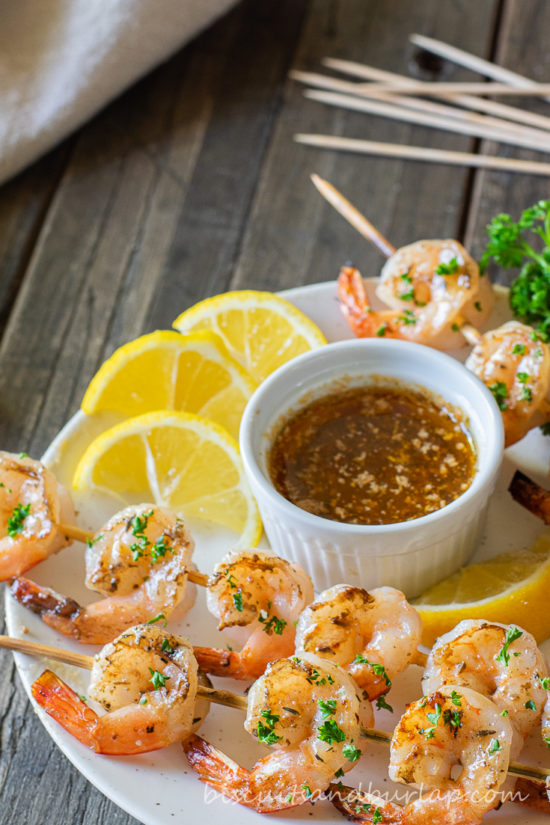 grilled shrimp skewers with sauce & lemons