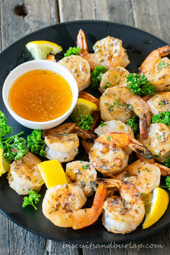 grilled shrimp with lemon on plate with sauce