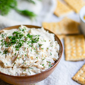 bowl of smoked fish dip with crakcers and lemon