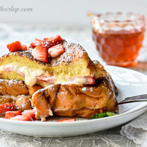 plate of stuffed french toast with syrup behind