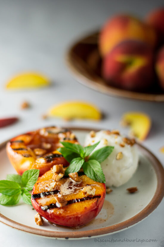 grilled peaches on plate with mint leaves