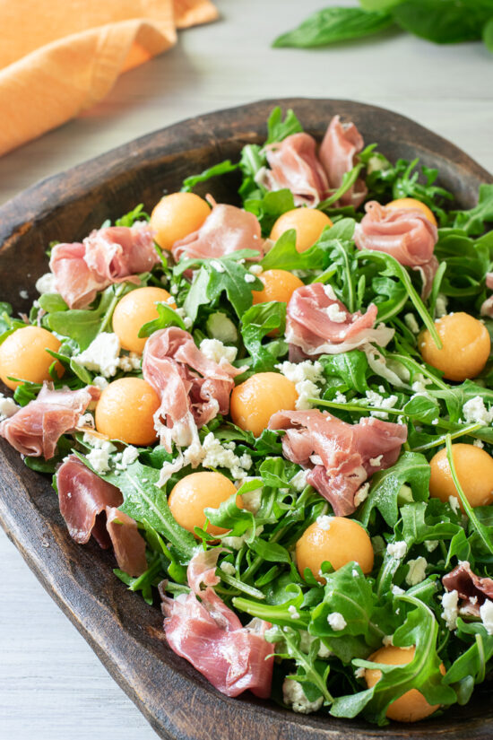 melon and prosciutto salad in wood bowl