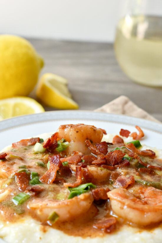 shrimp & grits with wine and lemon behind