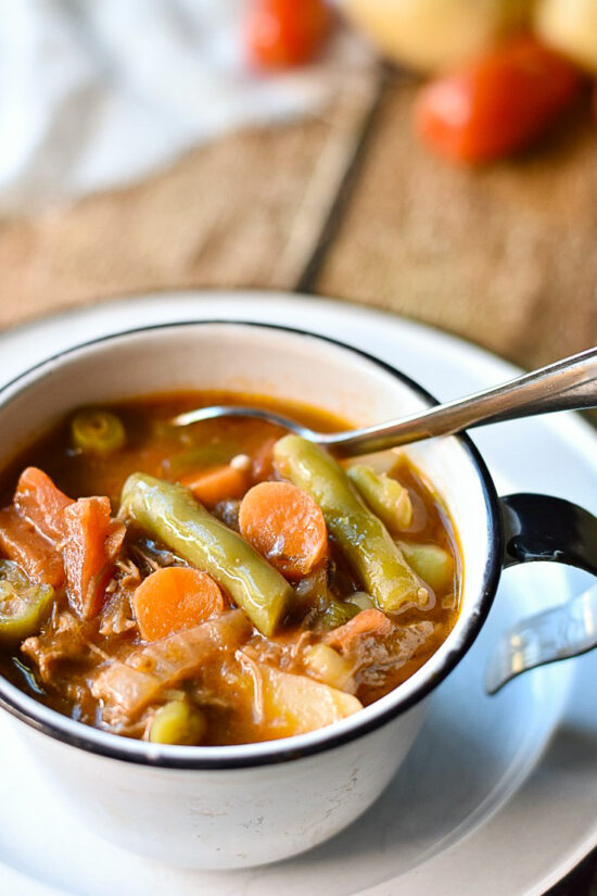 vegetable beef soup in cup with spoon