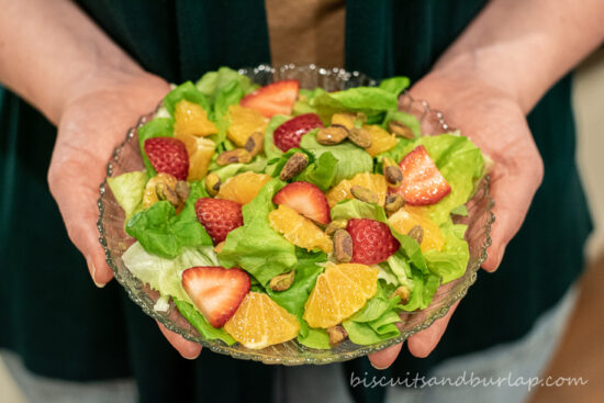 hands holding a salad with tangerines & strawberries