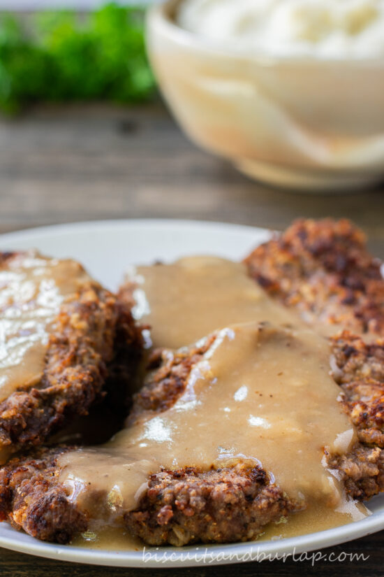 country fried steak on plate with potatoes behind