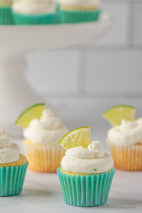 key lime cupcakes on counter and more behind on stand