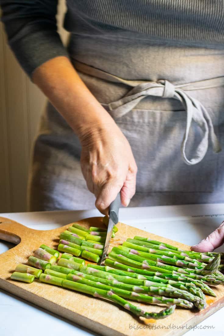woman in apron cutting asparagus
