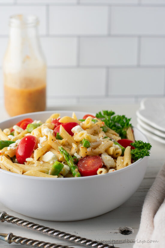 bowl of pasta salad with dressing behind