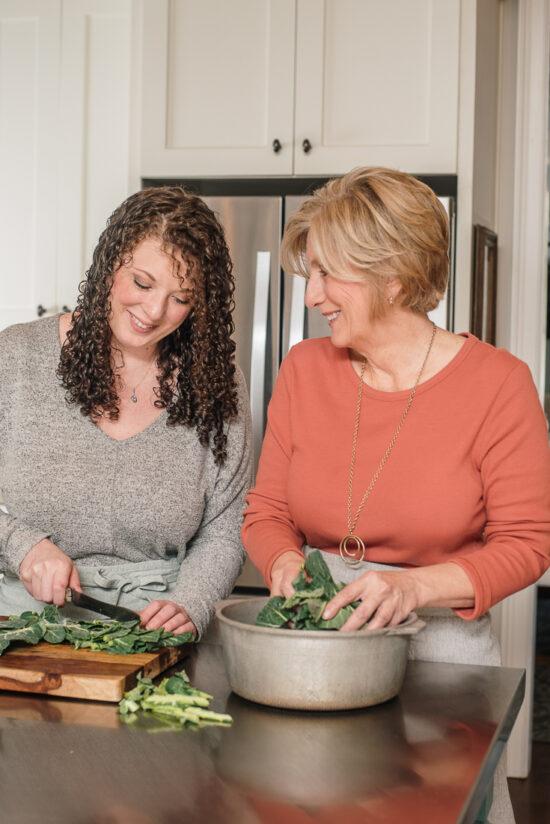 two women chopping collard greens