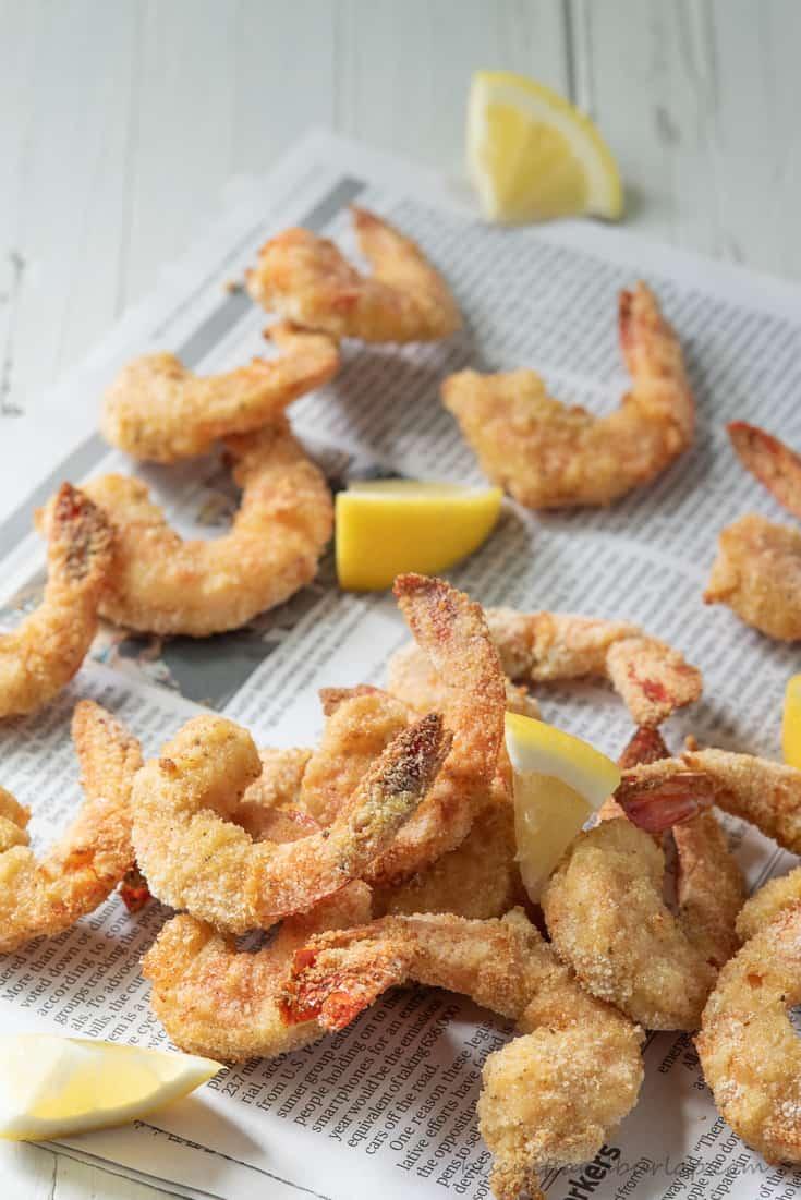 air fryer shrimp on newspaper with lemons