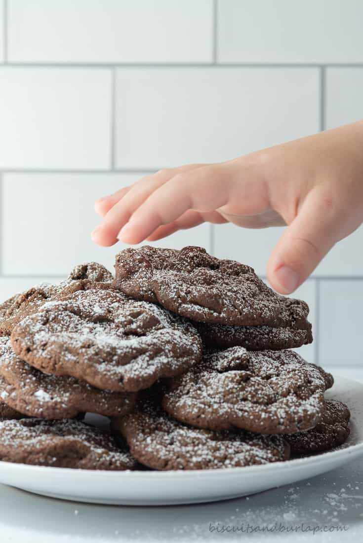 child's hand reaching for chocolate cookies