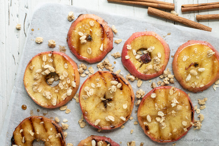 rows of grilled apples with granola and cinnamon sticks