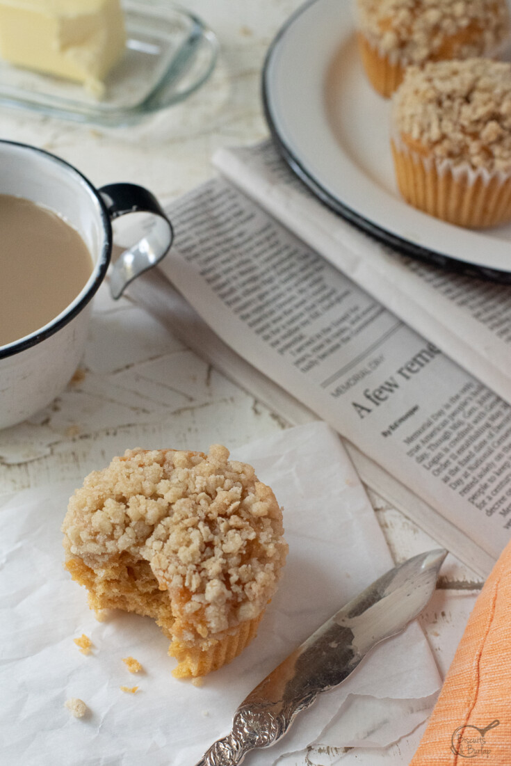 muffin with bite out, coffee & newspaper